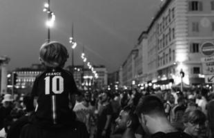 Image en noir et blanc derrière une foule de fans de sport qui bordent les rues de France.