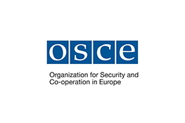 The Organisation for Security and Cooperation in Europe logo - four blue squares with the white text 'O.S.C.E' inside, under which there is the black text 'Organisation for Security and Cooperation in Europe'.