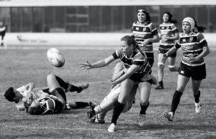 Imagen en blanco y negro de jugadoras de rugby en la cancha. Mientras dos yacían en el césped y cinco mujeres corrían hacia la pelota de rugby.