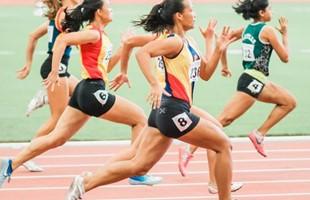 Cinq femmes courant sur une piste d'athlétisme. La vue est de côté au passage des coureurs.
