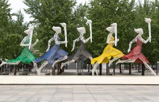 Sculpture olympique de 5 femmes courant avec la torche olympique