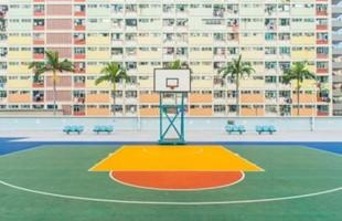 Terrain de basket vide en face d'un immeuble d'appartements.