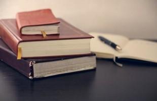 Libros y bolígrafo sobre el escritorio.