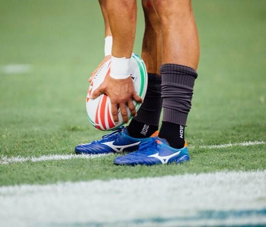 Joueur de rugby masculin tenant un ballon de rugby alors qu'il le place sur le sol.