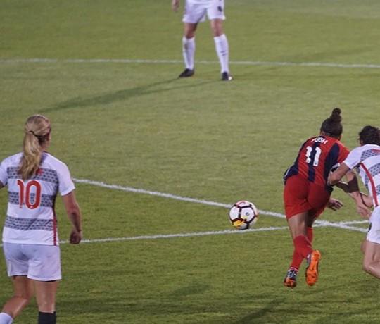 Footballeuses sur un terrain en herbe en direction du football.