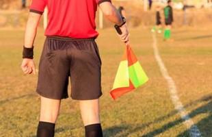 Image de l'arrière d'un juge de lignes debout à l'écart du terrain de football avec des joueurs au loin.
