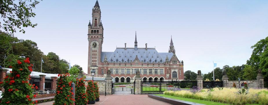 Une photographie du Palais de la Paix à La Haye, aux Pays-Bas. Un bâtiment orné du début des années 1900, il a une tour de l'horloge à une extrémité.