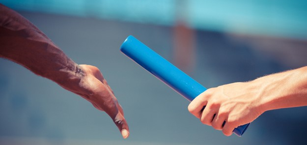 Image en gros plan d'un témoin de relais passant d'une main à une autre.