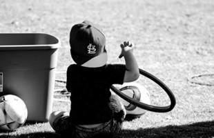 Imagen en blanco y negro desde atrás del niño sentado en el césped junto a balones de fútbol.