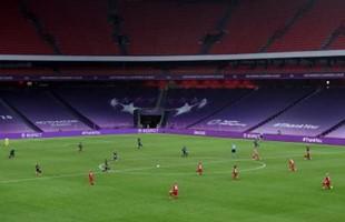 Los jugadores de fútbol arrodillados sobre césped en el estadio de fútbol.