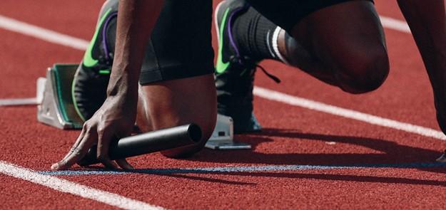 De cerca la imagen de un atleta arrodillado en el punto de inicio de una pista de atletismo, con un bastón de relevo en la mano.