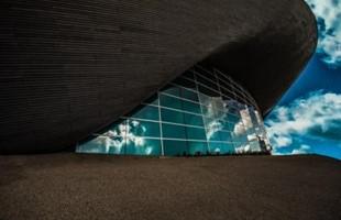 Imagen exterior del lateral de un edificio con paneles de vidrio que reflejan un cielo azul brillante y nublado.