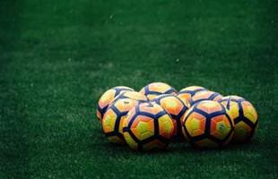 Imagen de nueve balones de fútbol agrupados en el suelo de una cancha de césped.