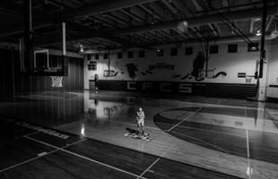 Image en noir et blanc du basketteur seul sur un terrain de basket à l'intérieur.