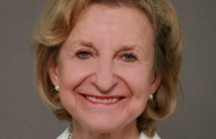 El rostro de una mujer sonriente con cabello rubio corto, lápiz labial rojo y aretes de perlas.
